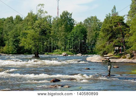 KOTKA, FINLAND - JUNE 26, 2016: Fisherman near Langinkoski Rapid on Kymi River next to The Russian Emperor Alexander III fishing lodge. On the background tourists take pictures.