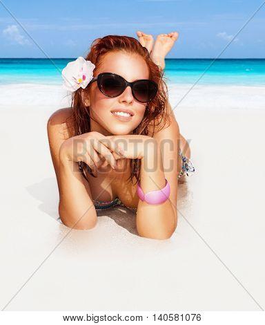 Beautiful woman on the beach, happy girl lying down on perfect white sandy coast sunbathing, happy summer vacation