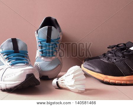 sports set of black orange sport shoes and blue sport shoe and shuttlecocks on sport background in concept family activity