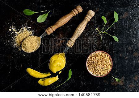 Mustard seeds powder and ready mustard spice on a dark background