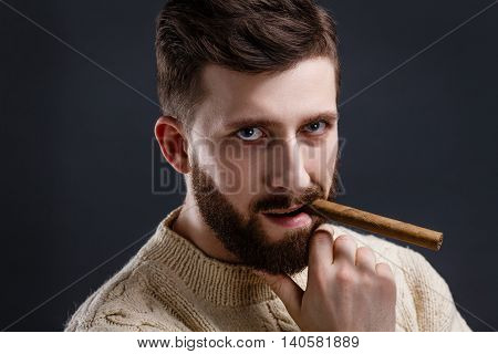 Portrait of handsome serious bearded man in white sweater holding cigar on black background