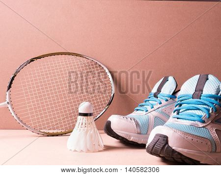 sports set of blue sport shoes and shuttlecocks with badminton racket on sport background in concept family activity