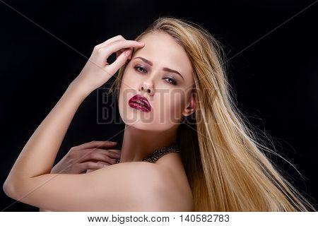 Portrait of blonde woman looking at camera against of black background