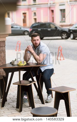 Youg man waiting for his order or friends. Handsome man sitting at wooden table in outdoor vegan cafe and looking at camera.