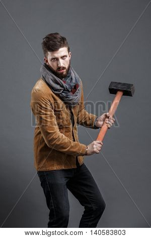 bearded man with hammer on black background