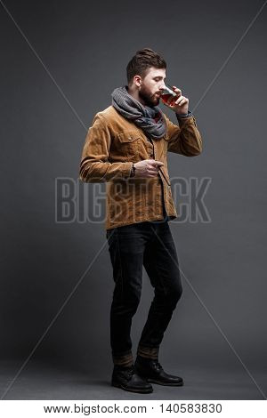studio shot of bearded man with cigar and glass of whisky posing against of grey background