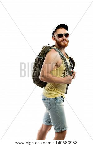 Side view of bearded traveler in sunglasses with backpack walking in trip. Studio shot. Isolated