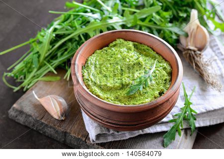Homemade arugula pesto in a rustic bowl