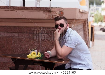 Portrait of handsome man in sunglasses sitting in outdoor vegan cafe and waiting for his business partners or best friends.