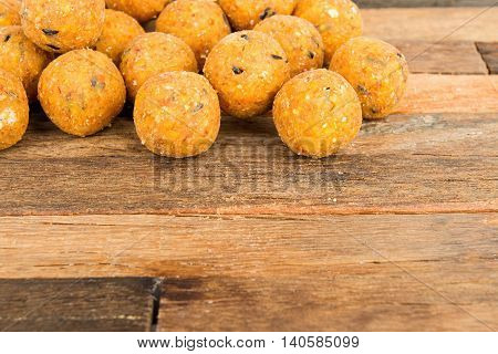 Boilies, fishing baits on wooden background. Macro shot.