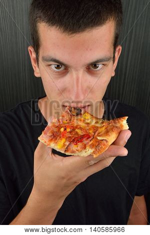 Portrait Of A Greedy Young Man Eating Pizza On A Dark Background. Fast Food, Unhealthy