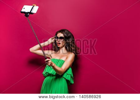 Portrait of young model in green dress and sunglasses posing while making selfie against red background.