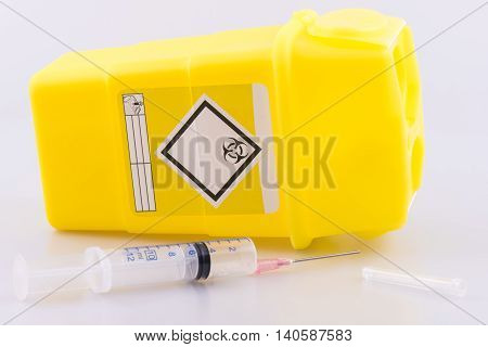 Hyperdermic needle and sharps bucket on a white background