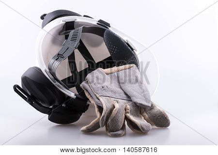 Underneath of hard hat showing head cradle with ear defenders and gloves on a white background