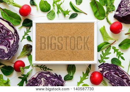 Vegetarian diet or clean eating concept background with a place for a text white frame surrounded various locally grown vegetables