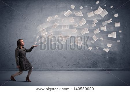 Caucasian businesswoman holding newspapers, which are floating away from his hands