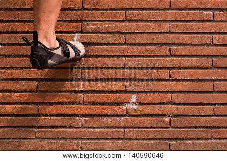 View of a fit climbing shoe by a man climbing a brick wall