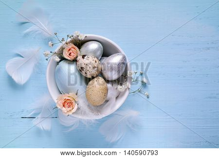 Easter eggs coloured in light pearl colours decorated with flowers and feather. Holyday decoration or maybe card. Focus on a bowl with eggs.