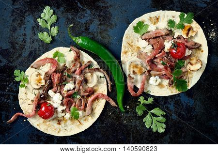 Tortillas filled with grilled beef soft cheese and mushrooms decorated with cilantro leaves