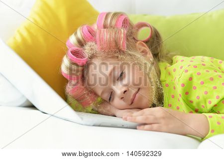 Happy cute little girl in hair curlers sleeping in her bed with laptop