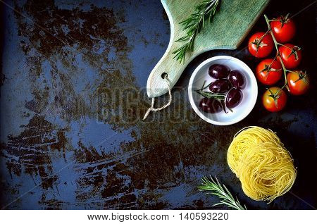 Culinary background with spaghetty olives tomatoes and spicy herbs