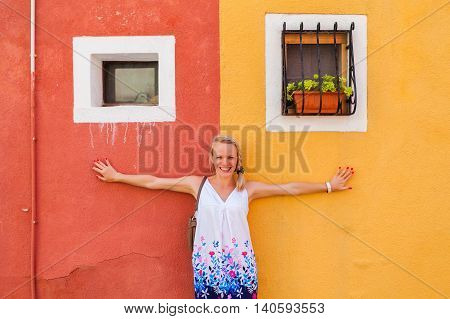 Woman traveler on the background of one of the many colored painted buildings of Burano Island, near Venice, Italy