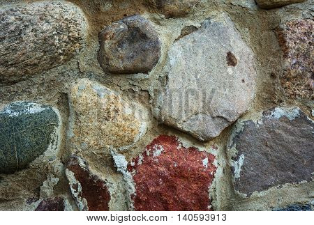 Wall built of large fieldstone combined cement. Close horizontal view.