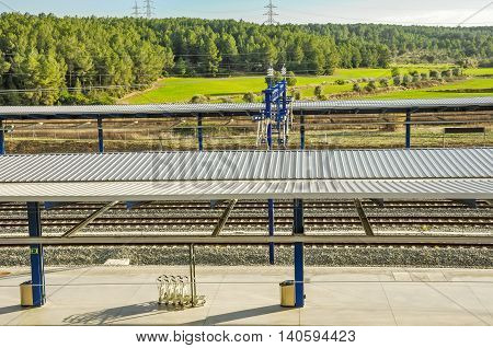 Platform of modern railway station Camp de Tarragona (Spain) with beautiful landscape. Horizontal.