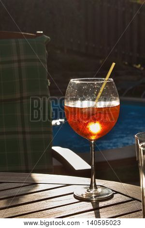 Cold summer drink by the pool. Party with refreshments by the pool. Alcohol drink with ice. Glasses with a refreshing drink. Alcohol at the party.
