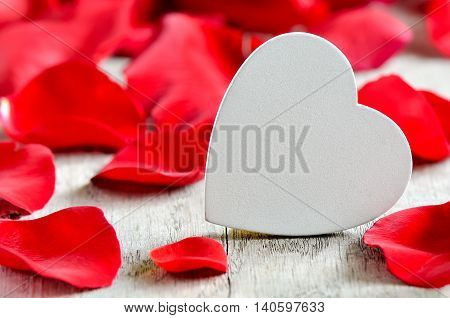 White wooden heart shaped board with free space for your text surrounded with rose petals
