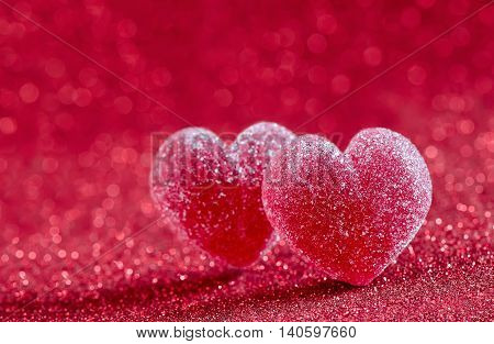 Marmalade hearts covered with sugar on a sparkling red background