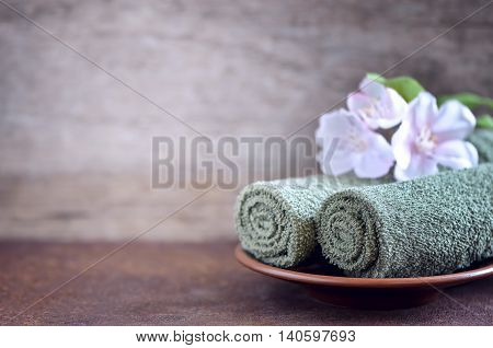 Green towels decorated with spring flowers spa concept sylized photo
