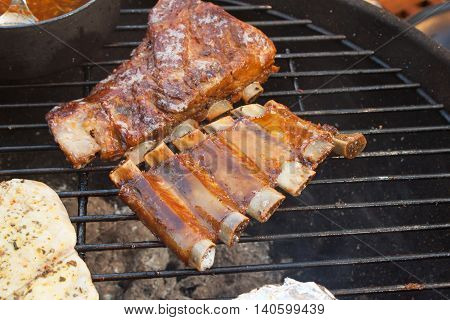 Grilled pork ribs on the grill. Marinated Grilled ribs on a summer party. Evening at a party.