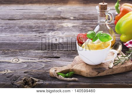 Quick simple breakfast snack for a few minutes in the microwave. Fragrant bright omelette with slices of white bread, herbs, juicy tomatoes with oil in white cup portions for healthy homemade food. With ripe peppers and basil. selective focus