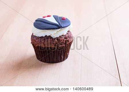 Delicious cupcake with tuxedo icon on it on wooden desk