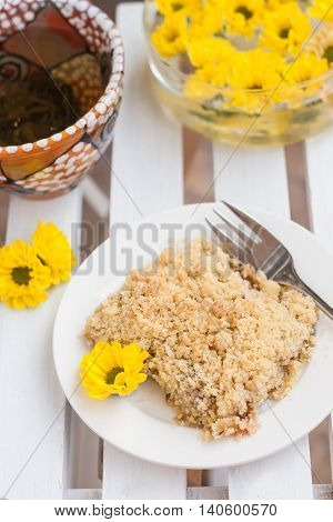 Piece Of Cake With Crumbs, Tea And Yellow Flowers On White Wooden Background