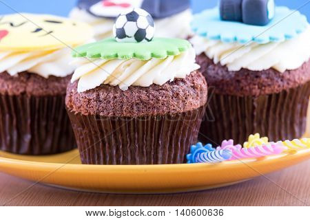 Delicious cupcakes with icons of ball tuxedo smiley and camera on it with yellow plate and three candles on wooden desk and blue background