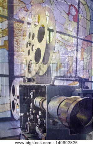 Old and antique commercial movie projector on a background of stained glass. Vintage projector. Mechanism of the aged theater projector.
