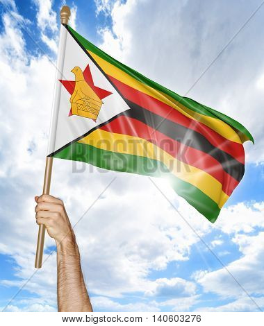 Person's hand holding the Zimbabwe national flag and waving it in the sky, 3D rendering