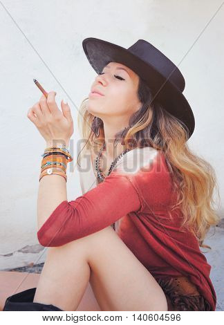 Beautiful woman enjoy smoking a cigarette, outdoor photo,  dressed in boho chic style outfit, long hairs, closed eyes, sitting on a street