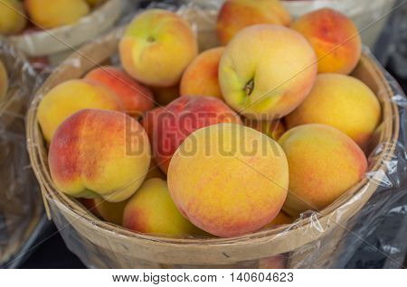 Basket of colorful organic peaches at local farmers market