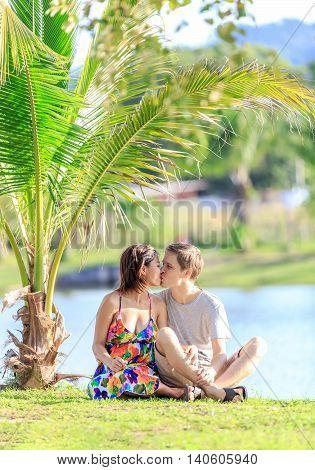 Young Couple Kissing In A Tropical Garden