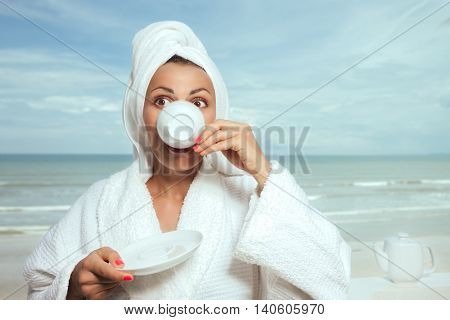 Funny cute young housewife hiding her face behind a cup of coffee