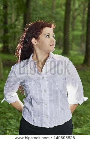 View of a young girl standing in a summer forest