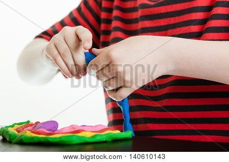 Hands Of A Young Boy Playing With Plastic Putty