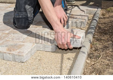 Paving stones are laid by a craftsman
