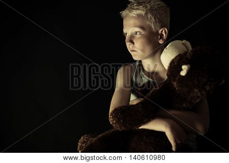 Introvert Little Boy In Dim Light Holding Toy
