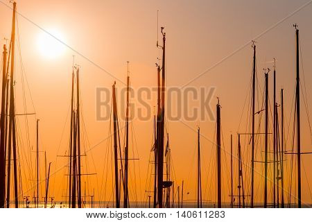 rows of boats at pier in the evening against sunset skies (sunset dusk lighting)