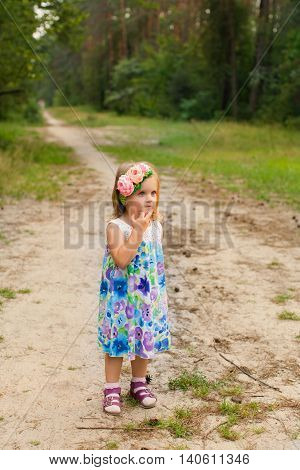 Portrait of a little girl in summer day outdoors