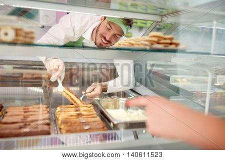 Male vendor in bakery taking out biscuit with cream from showcase